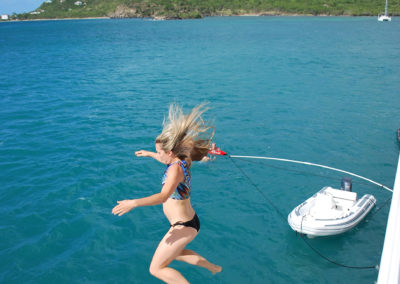 girl jumping of side of boat